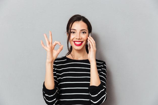 Portret van een glimlachende vrouw die op mobiele telefoon spreekt