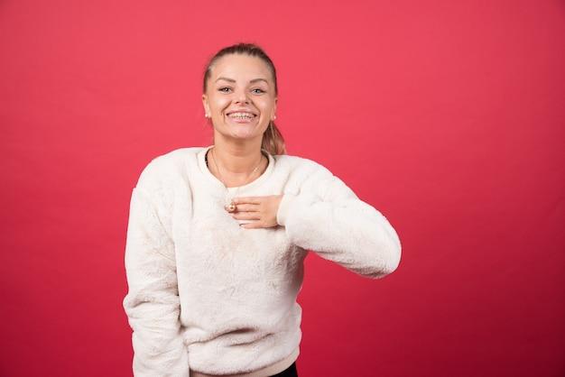 Portret van een glimlachende vrouw die op zichzelf richt