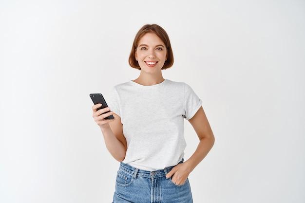Portret van een glimlachende vrouw die smartphone gebruikt, chat op sociale media, staat met mobiele telefoon tegen een witte muur