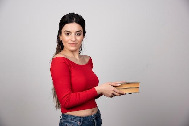 Portret van een glimlachende vrouw die twee boeken vasthoudt