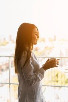 Portret van een glimlachende vrouw die van de ochtendkoffie in het balkon geniet