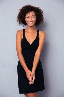 Portret van een glimlachende vrouw die zich over grijze muur bevindt