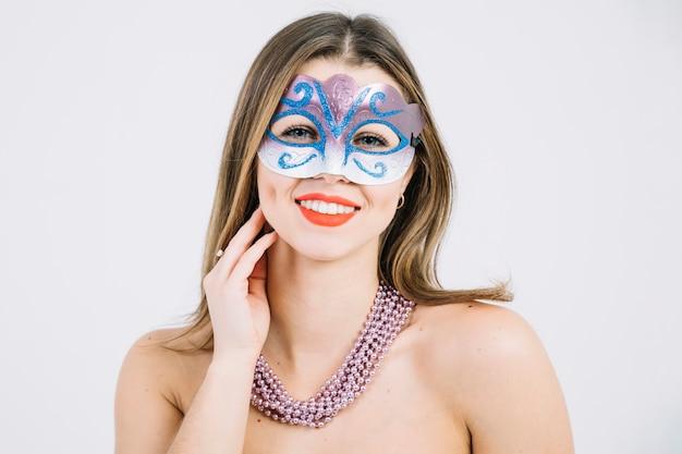 Portret van een glimlachende vrouw in carnaval-masker die halsband dragen