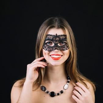 Portret van een glimlachende vrouw in carnaval-masker die halsband op zwarte achtergrond dragen