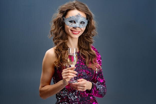 Portret van een glimlachende vrouw in een masker van carnaval en met een glas champagne zachtjes glimlachend. - afbeelding