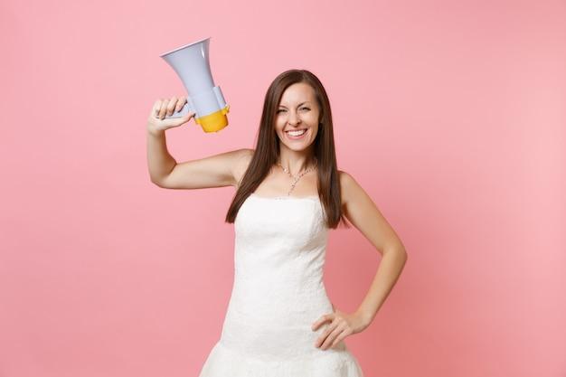 Portret van een glimlachende vrouw in een mooie witte kanten witte jurk die staat en een megafoon vasthoudt