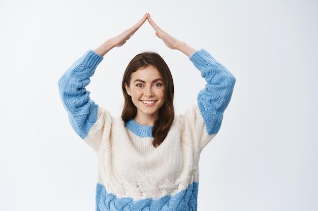 Portret van een glimlachende vrouw in een trui die het dak van het huis laat zien, handen op het dak maakt en er vrolijk uitziet aan de voorkant, witte muur