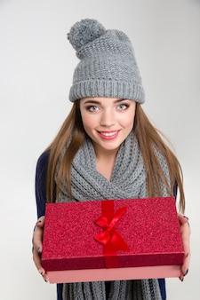 Portret van een glimlachende vrouw in winterdoek die geschenkdoos geeft op camera geïsoleerd op een witte achtergrond