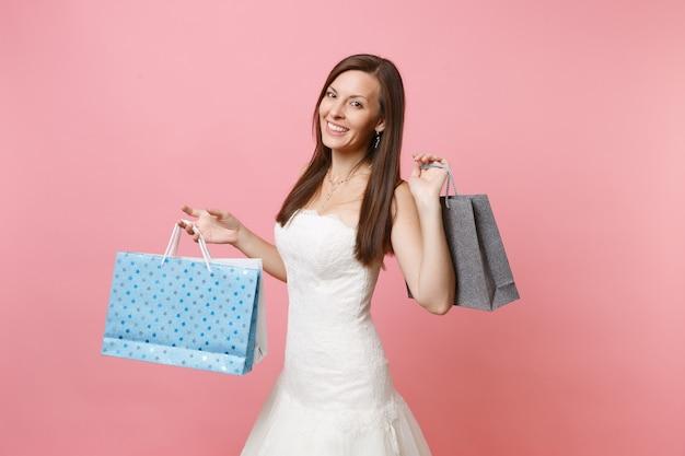 Portret van een glimlachende vrouw in witte kanten jurk met veelkleurige pakketten met aankopen na het winkelen