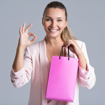 Portret van een glimlachende vrouw met boodschappentas en met goed teken.