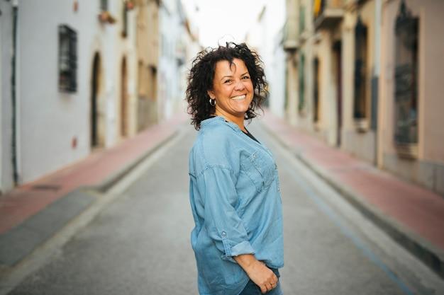Portret van een glimlachende vrouw van middelbare leeftijd op straat