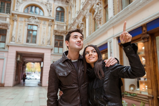 Portret van een glimlachende vrouw wijzende vinger op iets met haar vriend buiten in de oude europese stad