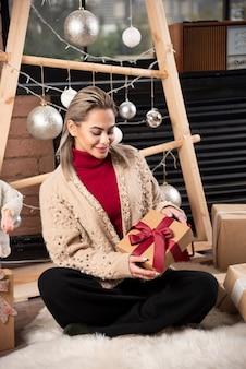 Portret van een glimlachende vrouw, zittend op een vloer met veel kerst geschenkdozen