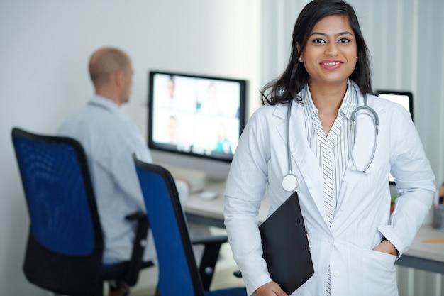 Portret van een glimlachende vrouwelijke huisarts met klembord in handen die in een medisch kantoor staat en naar de camera glimlacht