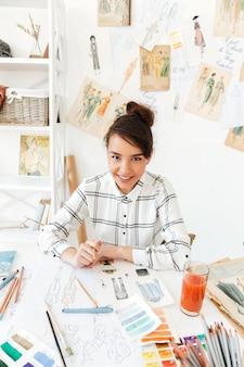 Portret van een glimlachende vrouwelijke modeontwerper schetsen maken