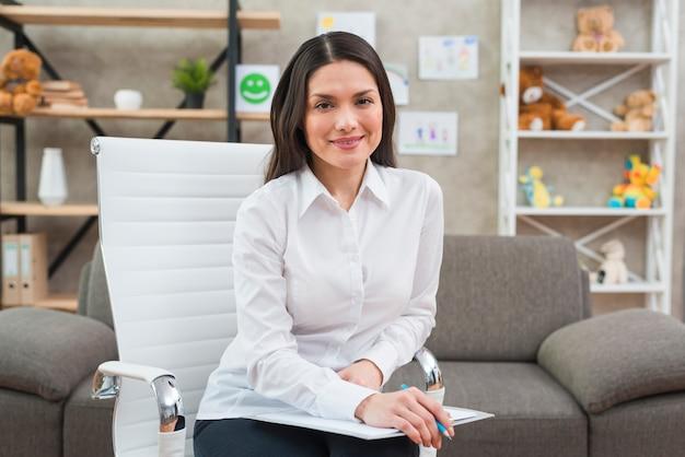 Portret van een glimlachende vrouwelijke psycholoog in haar kantoor