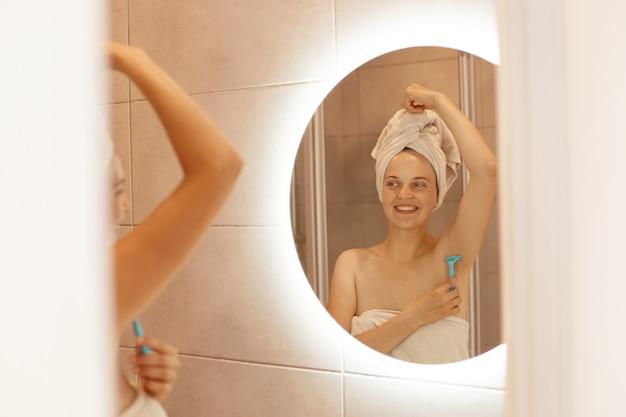 Portret van een glimlachende vrouwelijke scheeroksel in de badkamer, scheerapparaat in de hand houdend, kijkend naar de spiegelreflectie, gewikkeld in een witte handdoek, in de badkamer staan en ontharen.