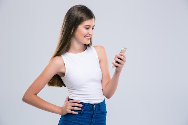 Portret van een glimlachende vrouwelijke tiener die geïsoleerde smartphone gebruikt