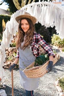 Portret van een glimlachende vrouwelijke tuinman bij de ingang van tuin
