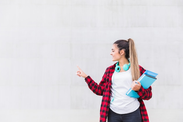 Portret van een glimlachende vrouwelijke universiteitsstudentholding boeken die in hand haar vinger op witte muur met exemplaarruimte richten