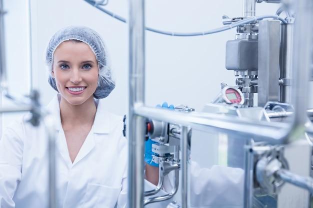 Portret van een glimlachende wetenschapper achter metaalpijp