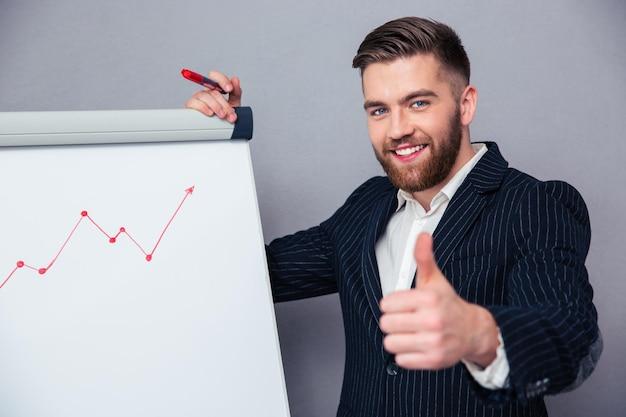 Portret van een glimlachende zakenman die duimen geeft terwijl grafiek wordt getrokken