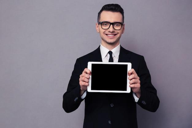 Portret van een glimlachende zakenman die het lege scherm van de tabletcomputer over grijze muur toont
