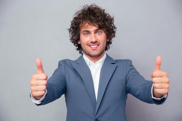 Portret van een glimlachende zakenman die zich met duimen bevindt die omhoog op een witte muur worden geïsoleerd