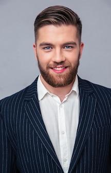 Portret van een glimlachende zakenman die zich over grijze muur bevindt