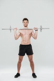 Portret van een glimlachende zekere sportenmens die een barbell houdt