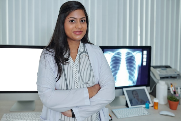 Portret van een glimlachende zelfverzekerde jonge arts die aan het bureau staat na het werken met longröntgenfoto's van de patiënt