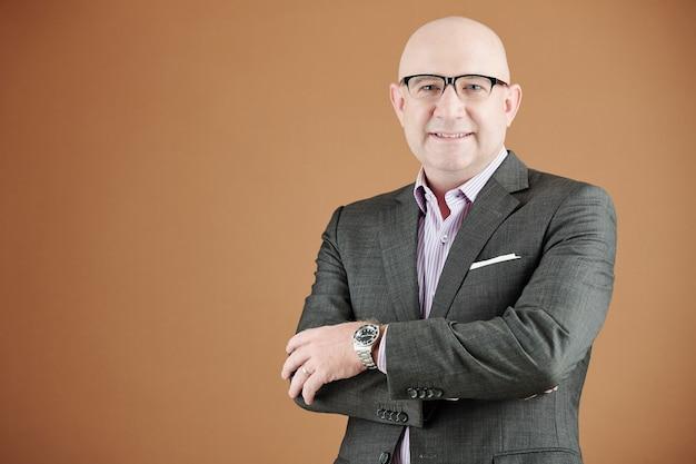 Portret van een glimlachende zelfverzekerde volwassen zakenman in een bril en een polshorloge met gekruiste armen tegen een bruine achtergrond