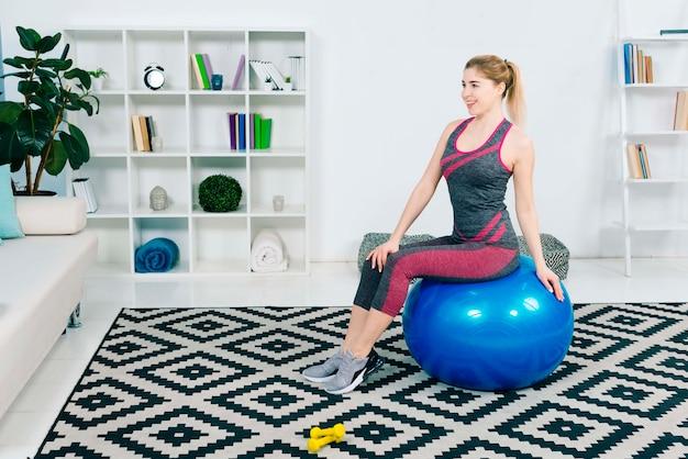 Portret van een glimlachende zitting van de geschiktheids jonge vrouw op blauwe pilatesbal die weg eruit zien