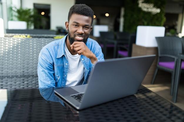 Portret van een glimlachende zwarte zakenman met laptop bij koffie