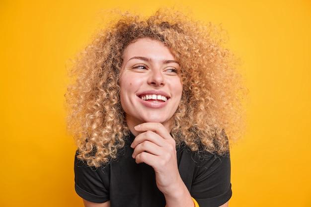 Portret van een goed uitziende oprechte vrouw houdt de hand op de kin glimlacht breed kijkt weg, drukt authentieke emoties uit