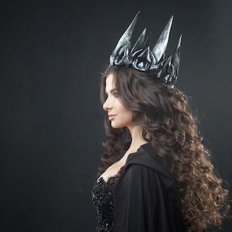 Portret van een gotische prinses. mooie jonge brunette vrouw in metalen kroon en zwarte mantel.