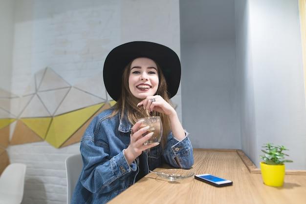 Portret van een grappig hipstersmeisje met een kop van koffie in hun handen.