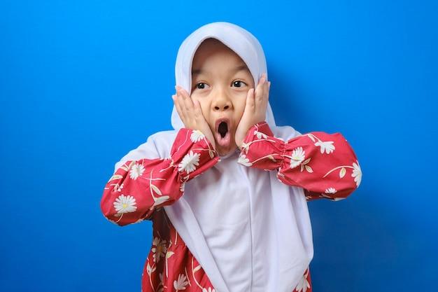 Portret van een grappig jong aziatisch moslimmeisje dat naar de camera kijkt met grote ogen die zijn mond bedekken, een geschokte, verbaasde uitdrukking tegen een blauwe achtergrond