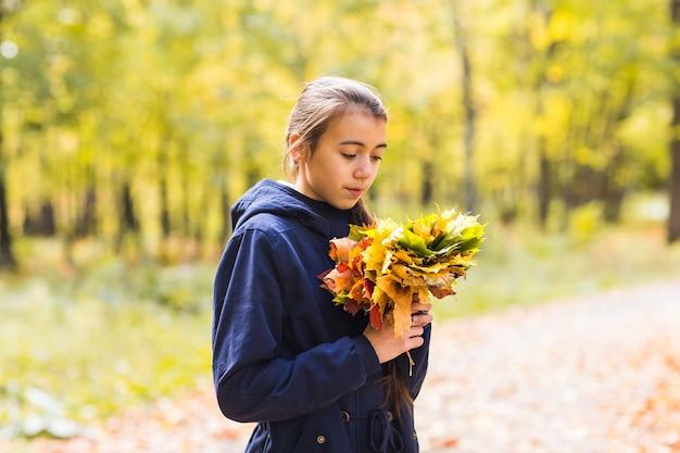 Portret van een grappig jong meisje in het de herfstweer in warme kleren en hoed