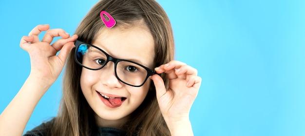Portret van een grappig kind schoolmeisje close-up kijken bril geïsoleerd op blauwe achtergrond.