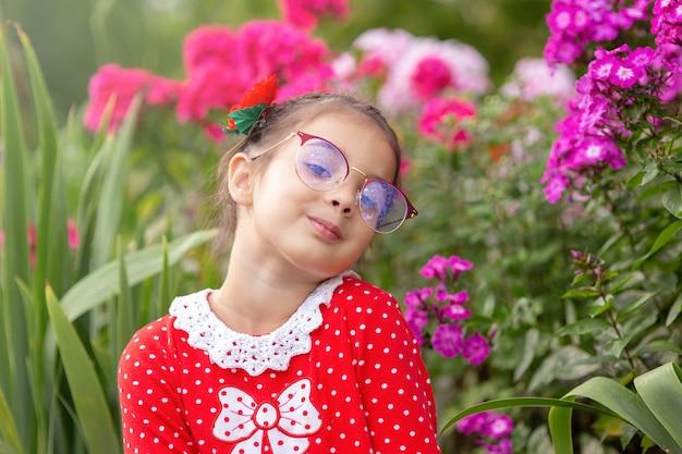 Portret van een grappig koket meisje in glazen, in een rode jurk met stippen, in de zomer bij een bloembed. horizontaal
