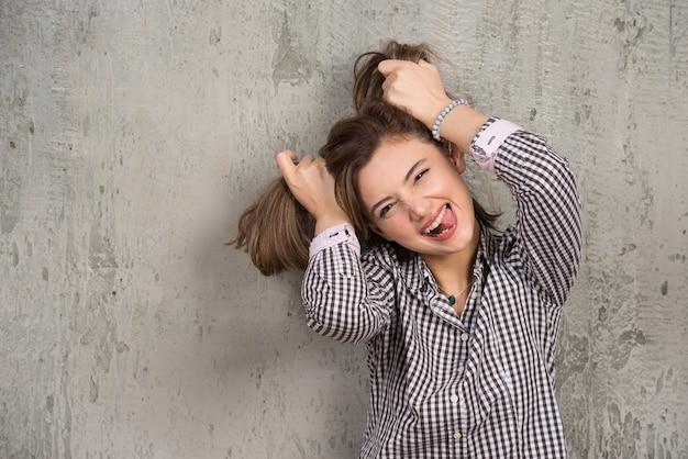 Portret van een grappig meisje dat twee paardenstaarten op het hoofd doet met haar handen.