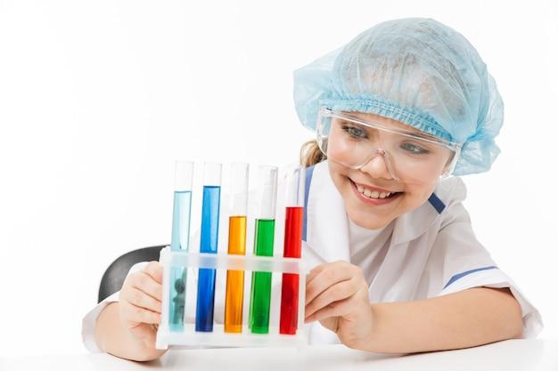 Portret van een grappig meisje in een witte laboratoriumjas die chemische experimenten maakt met veelkleurige vloeistof in reageerbuizen geïsoleerd over een witte muur