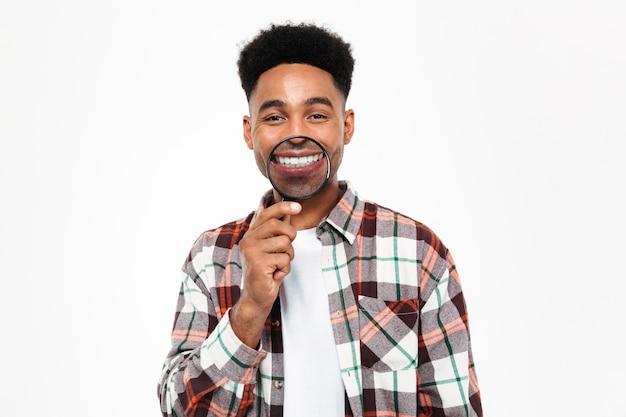 Portret van een grappige afrikaanse mens die met vergrootglas speelt