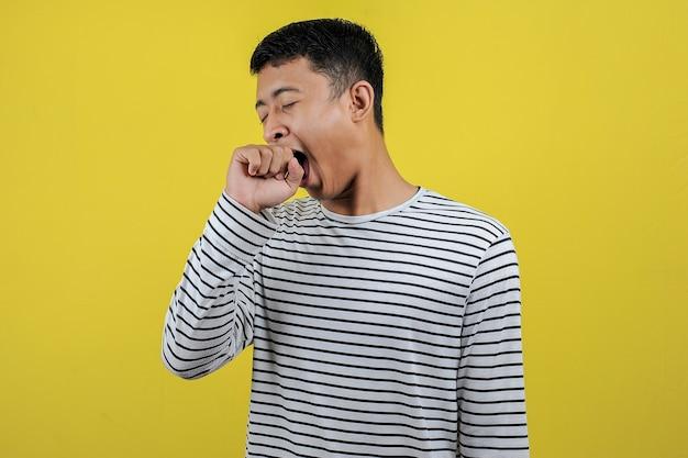 Portret van een grappige aziatische man die geeuwen met open mond en een slaperig gebaar toont. moe voelen van hard werken, geïsoleerd op gele achtergrond
