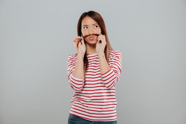 Portret van een grappige aziatische vrouw die met haar haar speelt