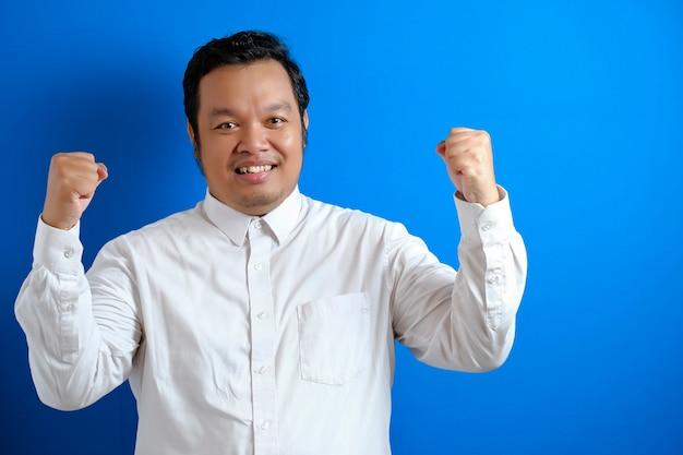 Portret van een grappige aziatische zakenman die trots glimlacht terwijl hij dubbele biceps laat zien, kracht boven vertrouwenconcept