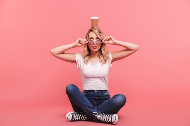 Portret van een grappige blonde vrouw met een vintage zonnebril die aan de voorkant glimlacht terwijl ze afhaalkoffie drinkt, geïsoleerd over een roze muur