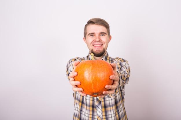 Portret van een grappige boer die pompoenen vasthoudt op een lichte studio als achtergrond