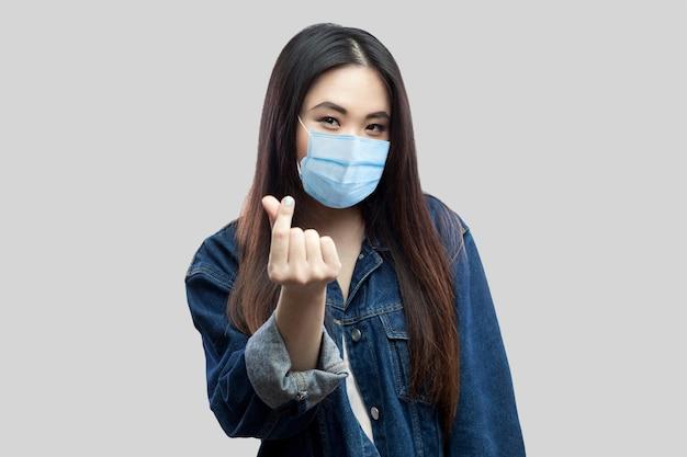 Portret van een grappige brunette aziatische jonge vrouw met een medisch masker in een casual blauw spijkerjasje dat staat en geldgebaar toont en naar de camera kijkt. studio opname, geïsoleerd op een grijze achtergrond.